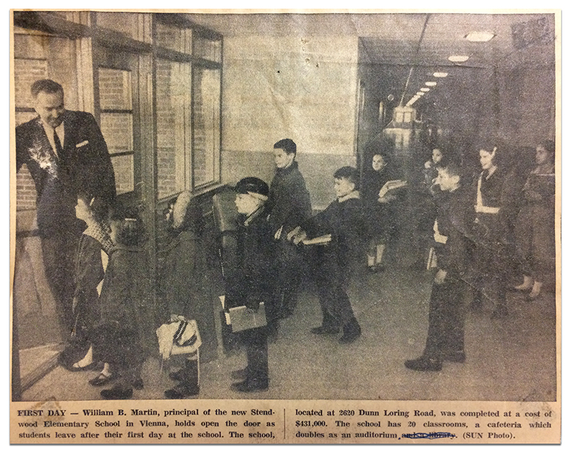 Newspaper clipping from February 1964, showing a black and white photograph of Principal William Martin holding open the door as students leave after their first day of school. The caption states that the school is located at 2620 Dunn Loring Road, and was completed at a cost of $431,000. The school has 20 classrooms, and a cafeteria which doubles as an auditorium.