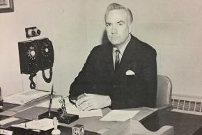 Black and white photograph of William Berkeley Martin, principal from 1963 to 1978, at his desk.